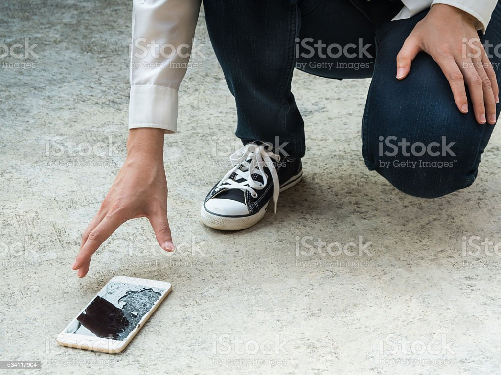 Person Picking Broken Smart Phone of Ground stock photo