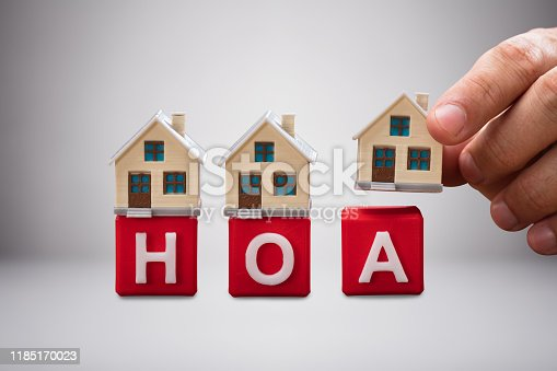 istock Person Placing The Miniature Houses On Red Hoa Blocks 1185170023