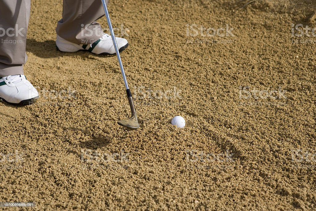 Person playing golf in sandy bunker, low section royalty-free stock photo