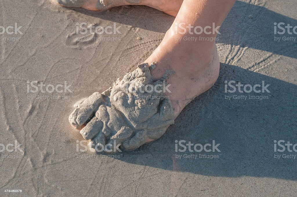 Person playing in the sand on a beach stock photo
