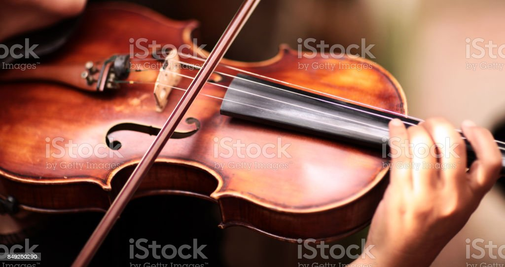 A person playing the violin showing hands holding the bow stock photo