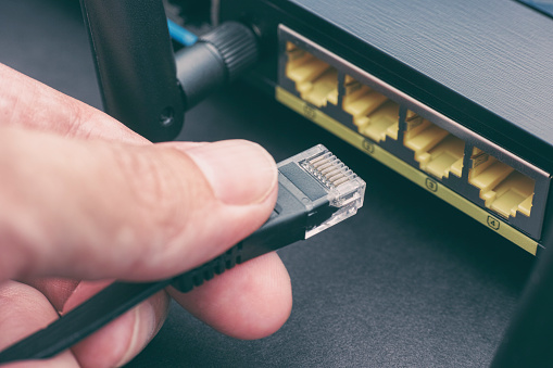 Person plugging in cable to wireless router. Close up.