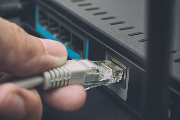 person plugging in cable to wireless router - kabel komputerowy zdjęcia i obrazy z banku zdjęć