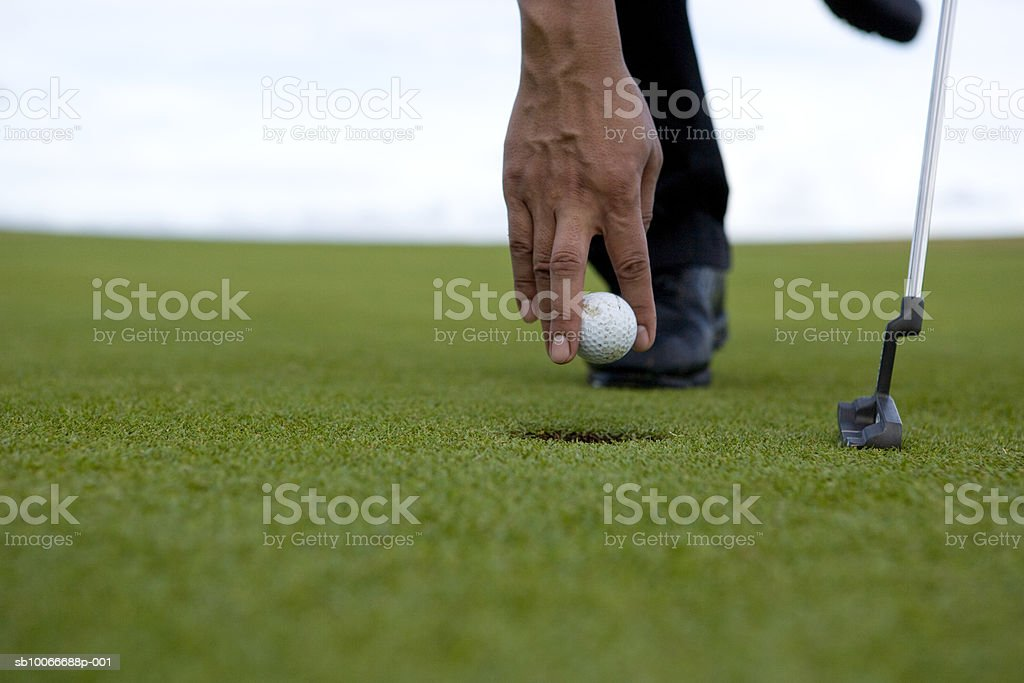Person positioning golf ball on golf course, low section (differential focus) royalty-free stock photo