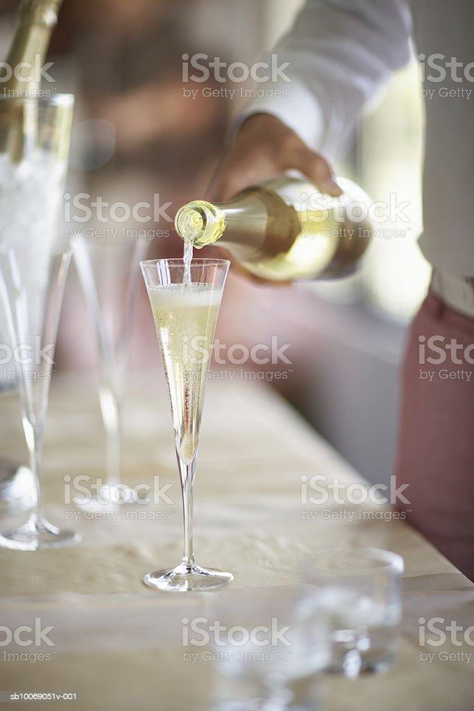 Person pouring champagne into glass, close-up, Mid section foto de stock libre de derechos
