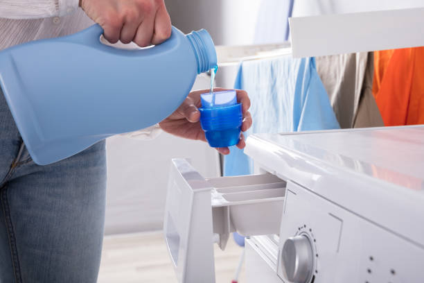 Person Pouring Detergent In Lid Close-up Of A Person's Hand Pouring Detergent In Lid laundry detergent stock pictures, royalty-free photos & images
