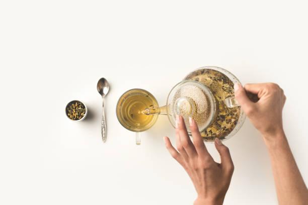 person pouring herbal tea - herbata ziołowa zdjęcia i obrazy z banku zdjęć