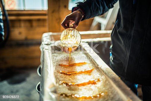 A close-up of a person at sugar shack pouring maple syrup onto snow to make maple sugar taffy