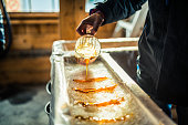 istock Person pouring maple syrup onto snow at sugar shack 925426372