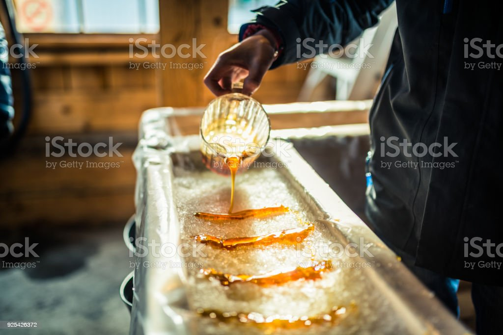 Person pouring maple syrup onto snow at sugar shack stock photo