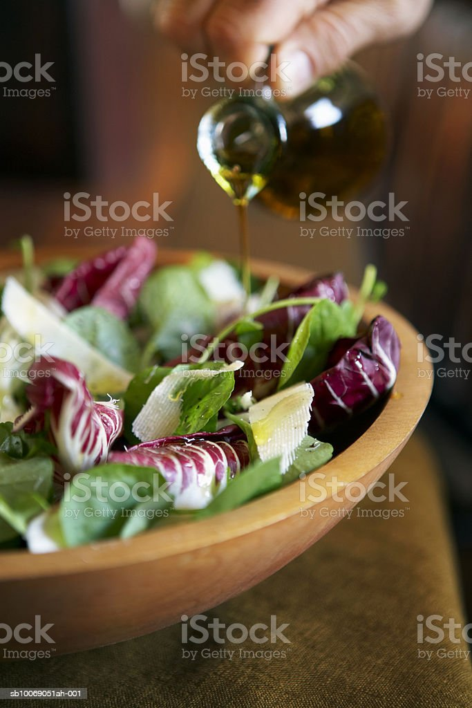 Person pouring oil onto salad in wooden bowl, close-up foto de stock libre de derechos