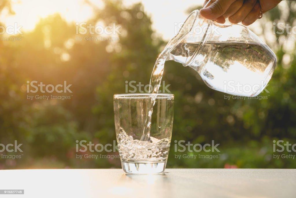 Person gießt Wasser aus Krug Glas auf Natur Hintergrund – Foto