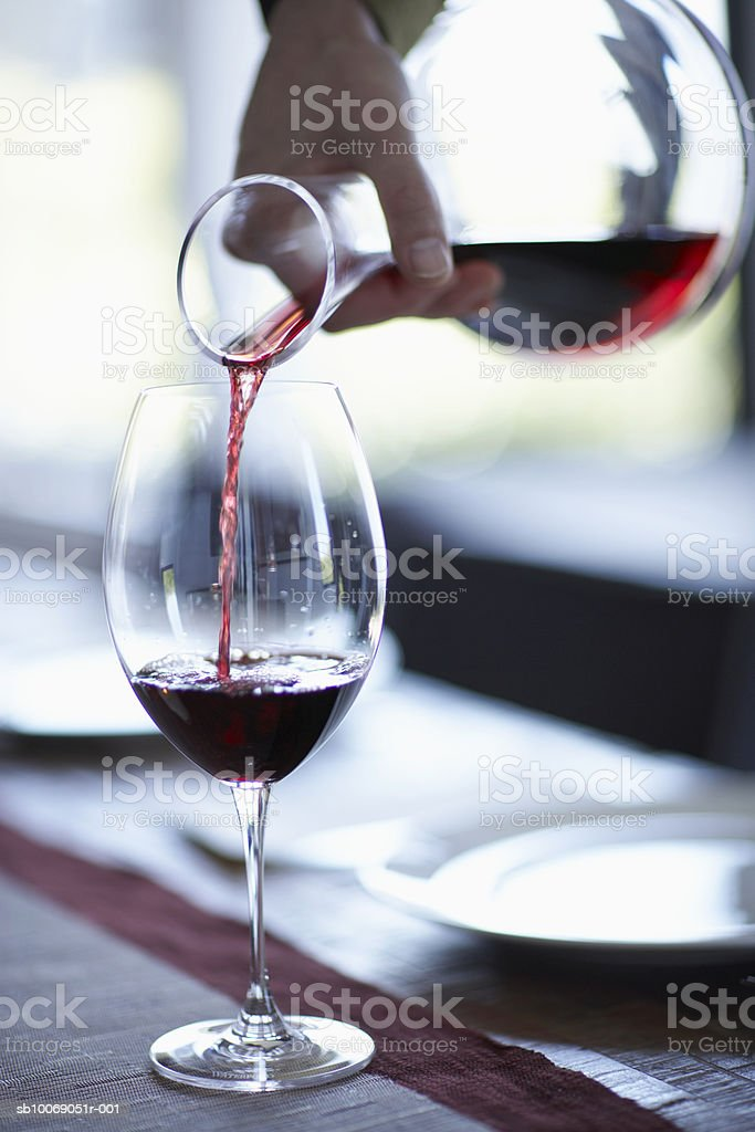 Person pouring wine from decanter into wine glass, close-up royalty-free stock photo