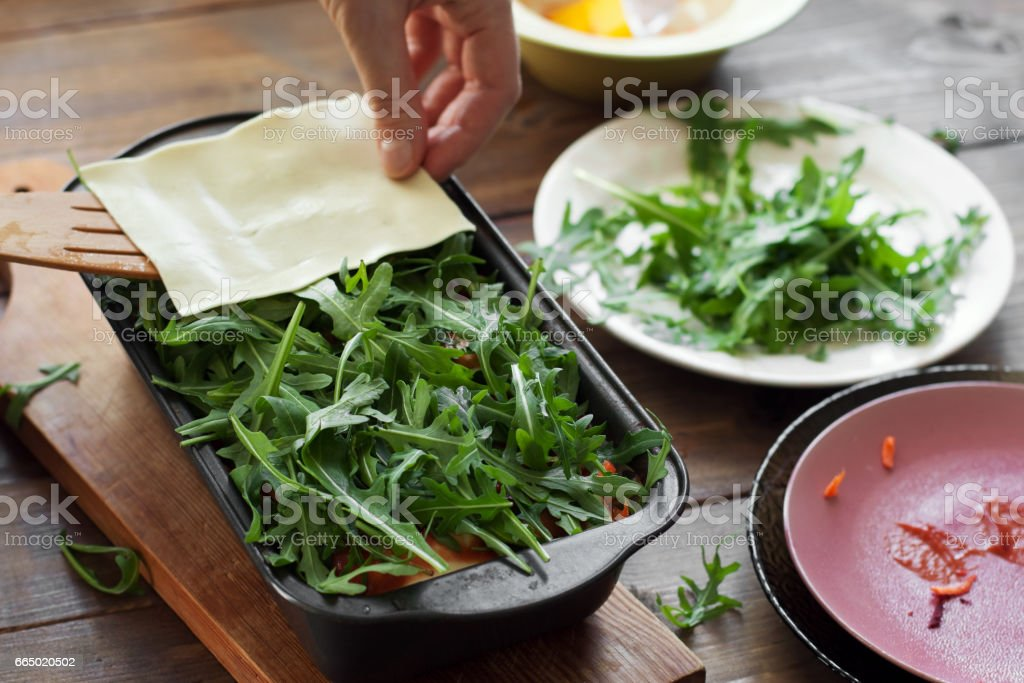 Person prepares vegetable lasagna, covers arugula with a dough sheet. stock photo
