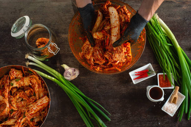 Person preparing Kimchi Person making Kimchi wearing black rubber gloves for protection kimchee stock pictures, royalty-free photos & images
