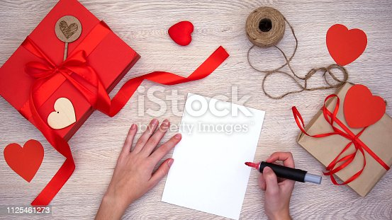 1125461272 istock photo Person preparing to paint on paper, hand-made gift boxes on wooden background 1125461273