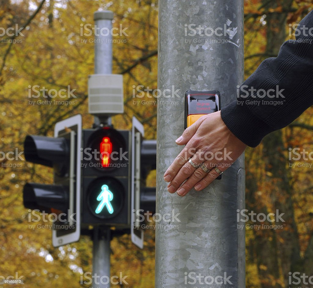 Person pressing the button to cross at a pedestrian crossing stock photo
