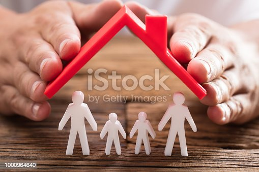 istock Person protecting family figures with roof 1000964640