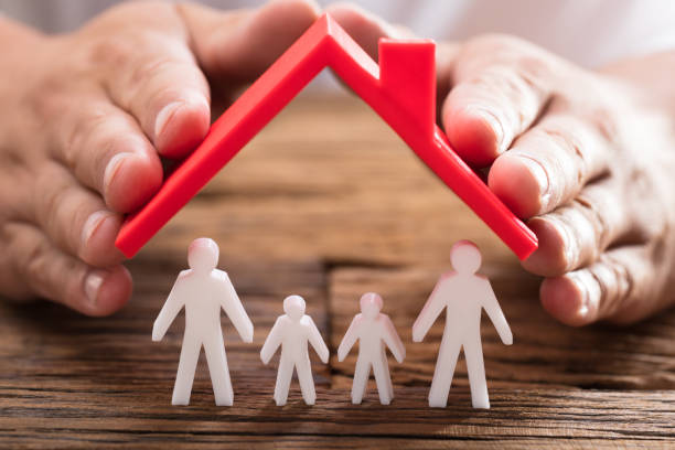 Person protecting family figures with roof A person's hand protecting family figures with red roof on wooden desk home insurance stock pictures, royalty-free photos & images