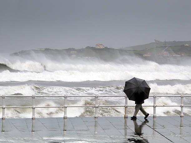 Persona de protección con paraguas en un día de lluvia y viento - foto de stock