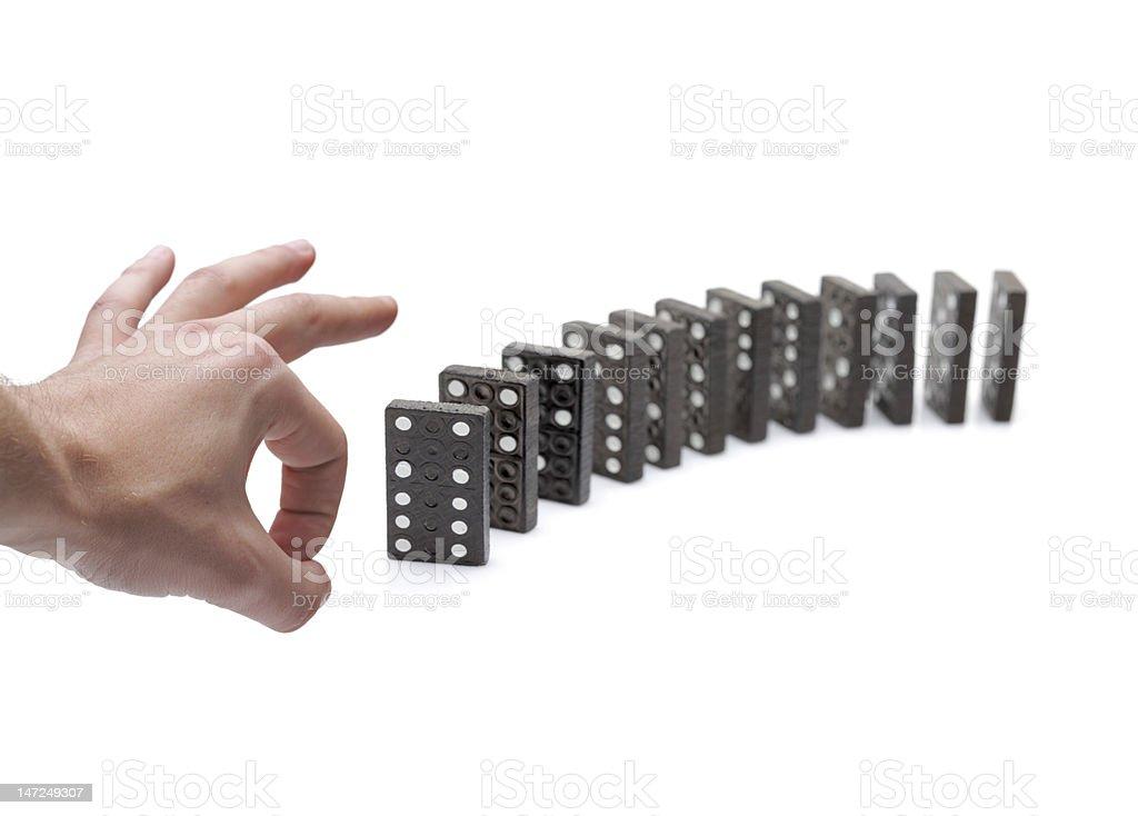 Person pushing domino blocks stock photo
