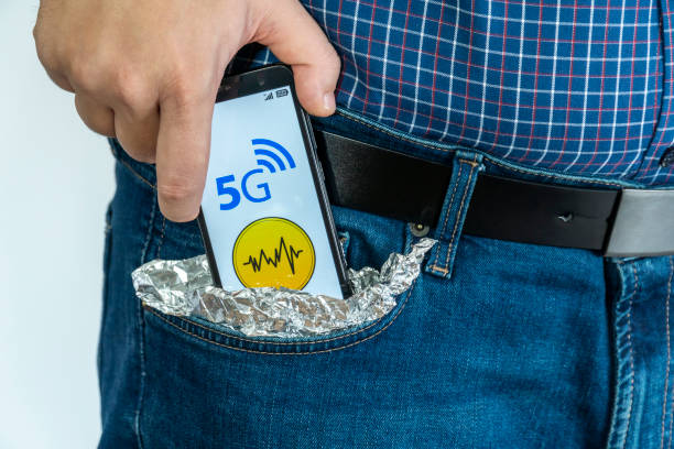 Person putting a smartphone in his pocket covered with foil stock photo