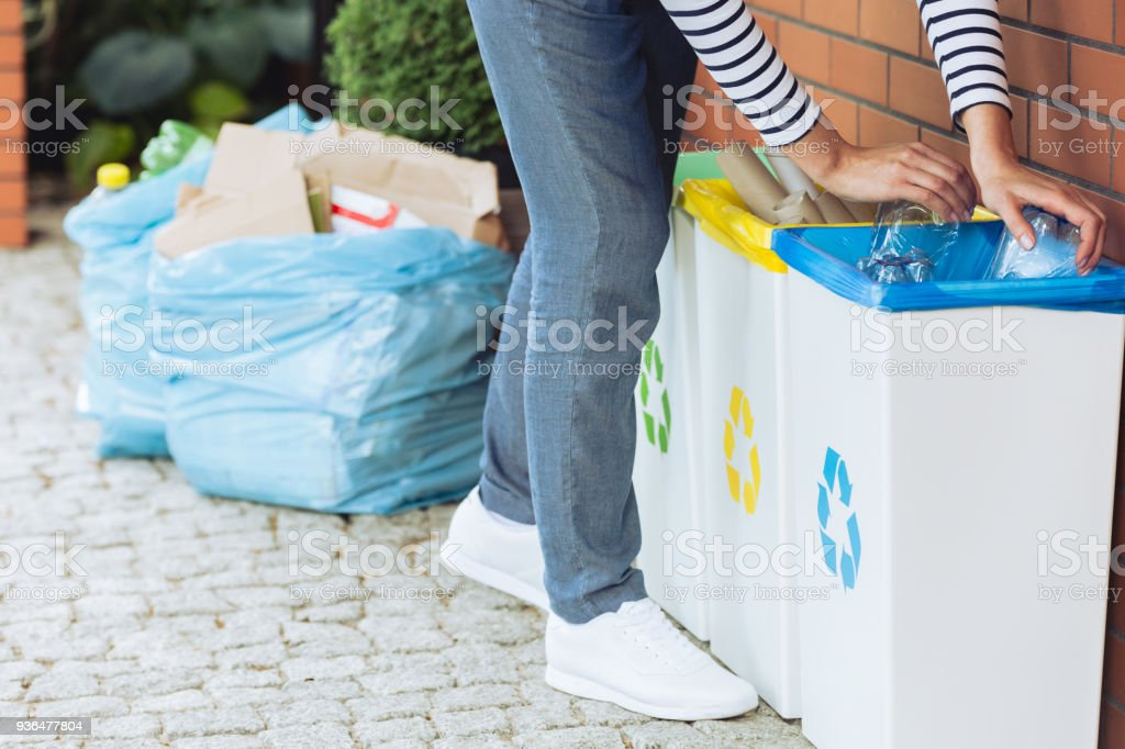 Person putting bottles into bin – zdjęcie