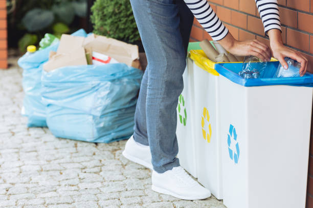 Person putting bottles into bin stock photo
