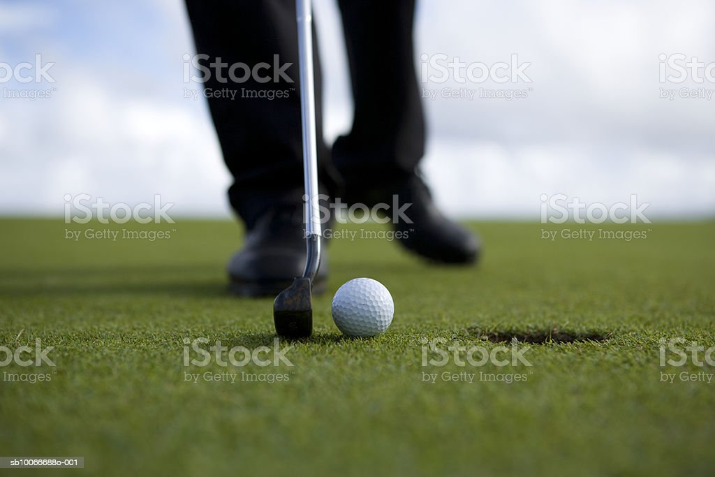 Person putting golf ball, low section (differential focus) royalty free stockfoto