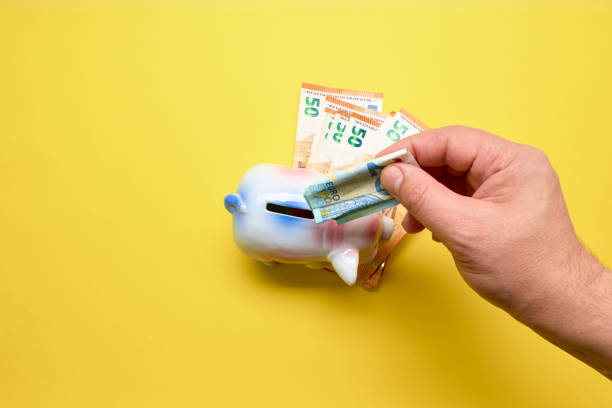 Person putting money in Pink Pig Money Box on a yellow background stock photo