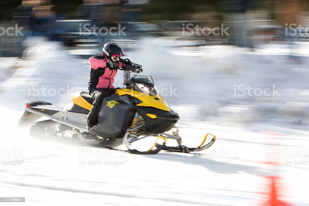 A person racing on a snowmobile stock photo