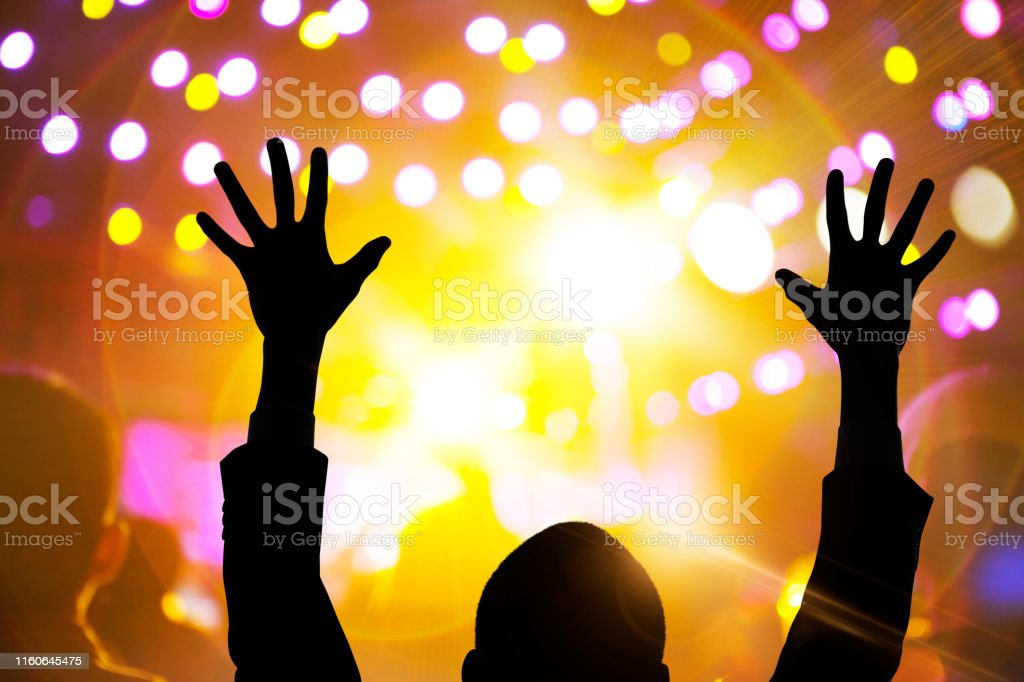 Person raising hands in night club party concert music festival