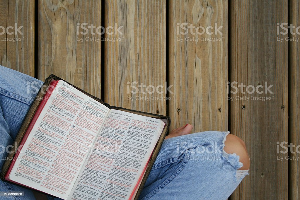 Person reading Bible on wooden deck stock photo