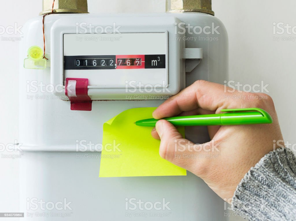 Person reading the gas meter in the private house, counter for distribution domestic gas. Selective focu. stock photo