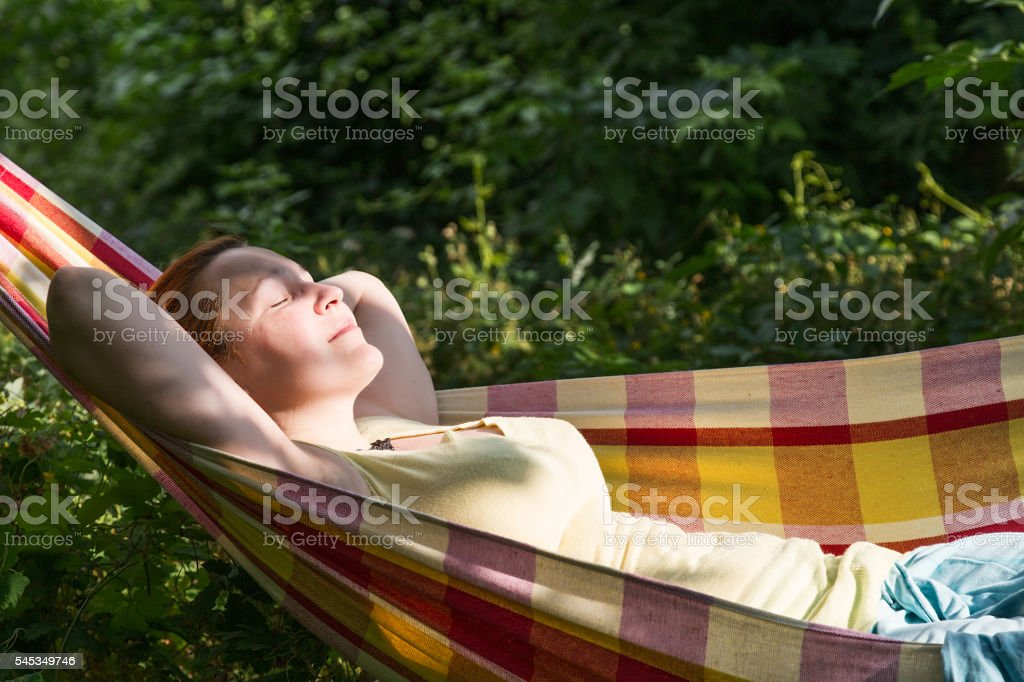 Person relaxing in Hummock at Summer Garden side View stock photo