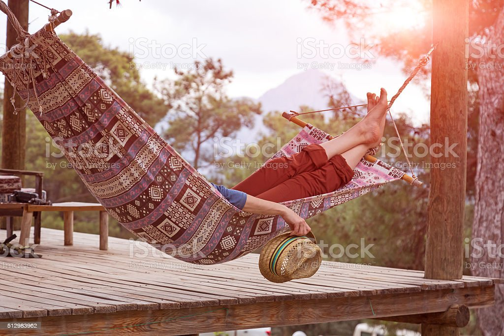 Person relaxing lying in Hammock at rural cottage garden stock photo