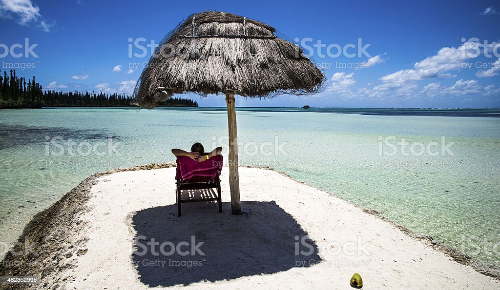 Person relaxing on a tropical beach stock photo