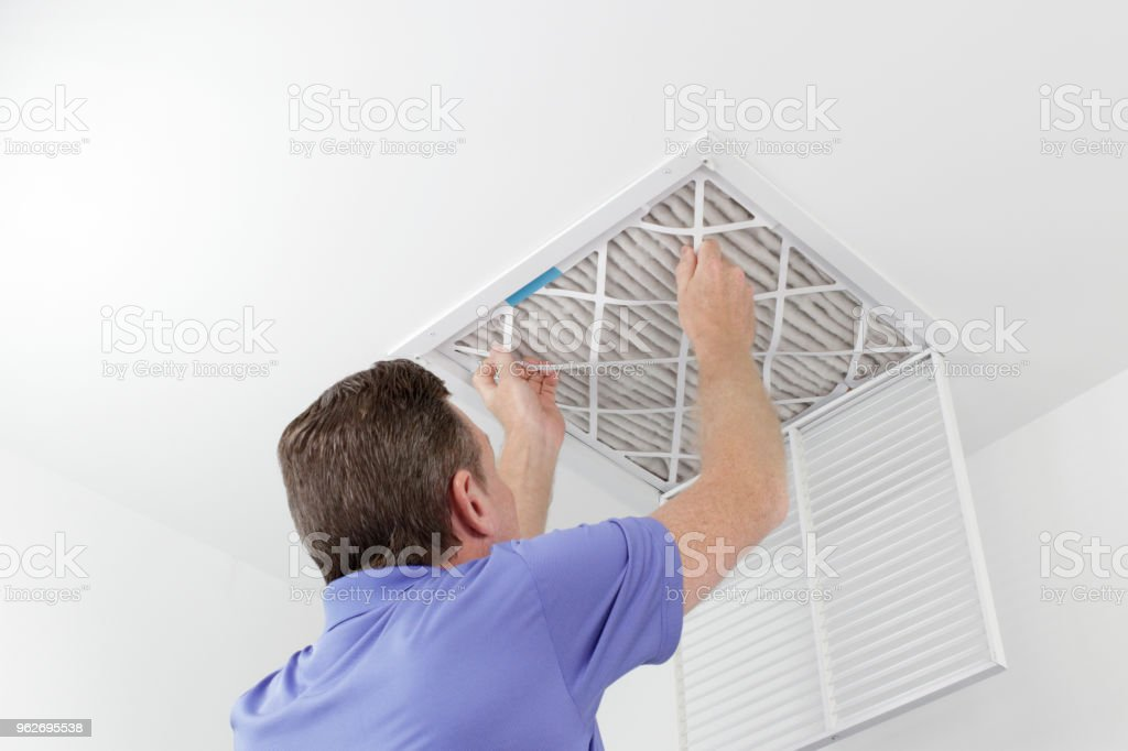 Person Removing Ceiling Air Filter stock photo
