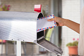 Closeup on a woman's hand as she is getting her post out of her letterbox