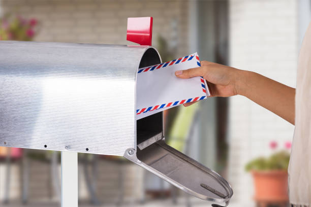 Person Removing Letter From Mailbox Close-up Of A Person's Hand Removing Letter From Silver Mailbox mailbox stock pictures, royalty-free photos & images