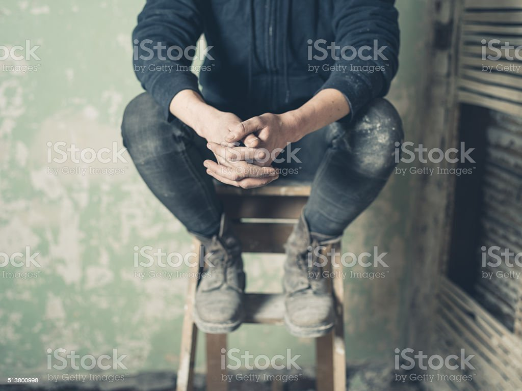 Person resting on stepladder stock photo