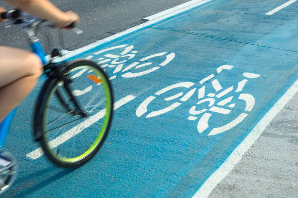 Person riding a bike on bicycle lane or cycle path outdoors stock photo