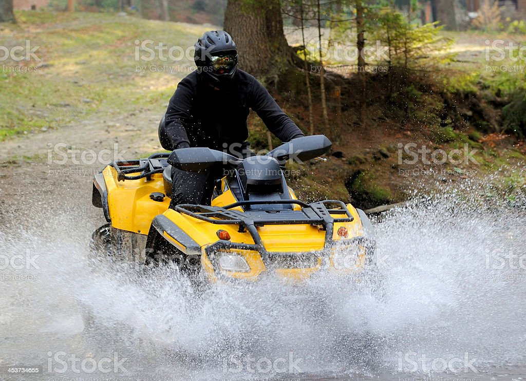 Person riding an ATV on a grassy trail stock photo
