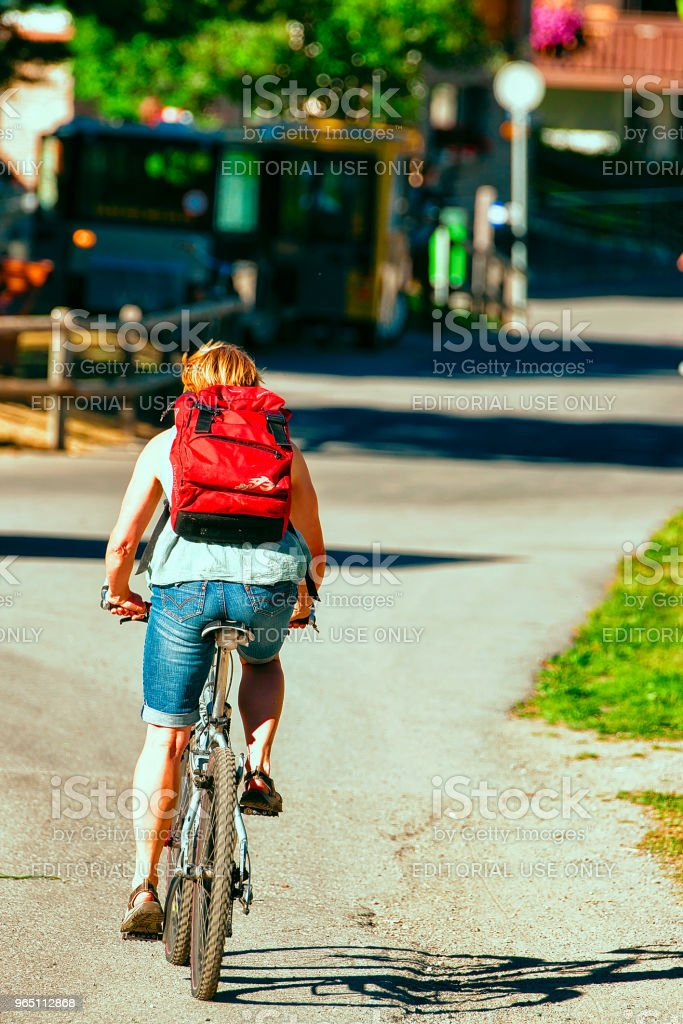 Person riding bicycle in resort city in Switzerland in CH royalty-free stock photo