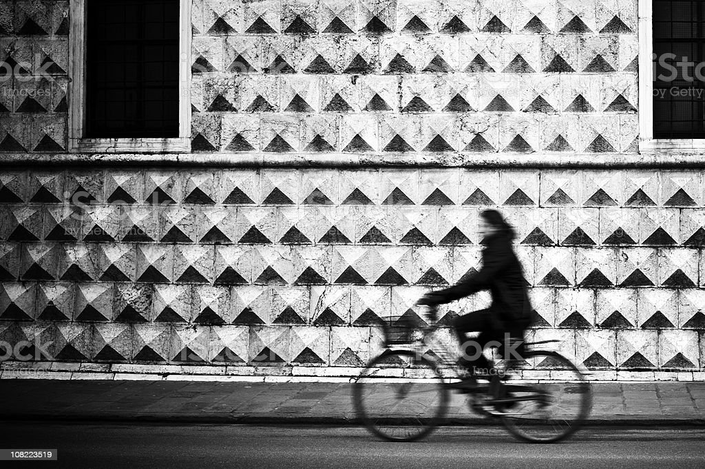 Person Riding Bicycle on Italian Street, Black and White royalty-free stock photo