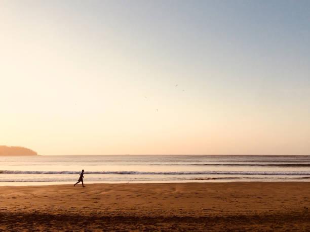 Person, die am Strand bei Sonnenuntergang - Jogger am Ozean – Foto