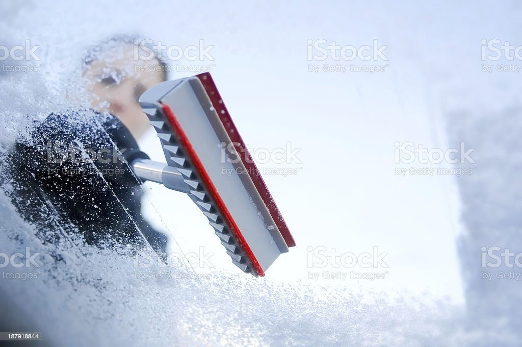 Person scraping ice from a windshield stock photo