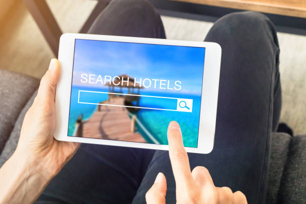 Person searching hotel room to book online with tablet computer - foto stock