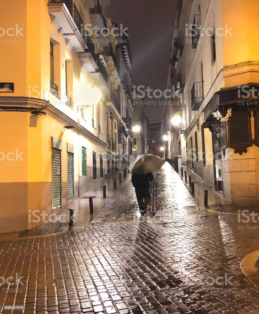 person seen from behind walking with an umbrella down an alley on a rainy night stock photo