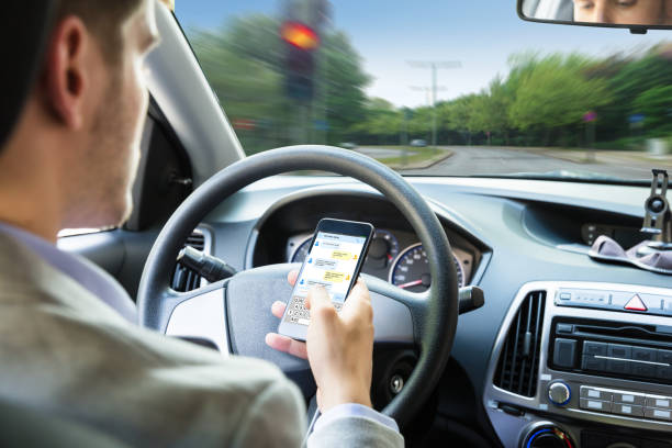 person sending text message by mobile phone while driving car - text messaging stock photos and pictures